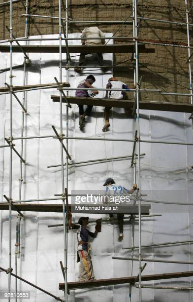 Iraqi workers build huge oil tanks at the Daura oil refinery on November 5 2009 in Baghdad Iraq Iraq and a grouping of US and European oil companies...