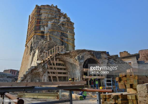 Iraqi workers build wooden support structures during the reconstruction of AlHadba leaning minaret in Mosuls warravaged old town on December 15 2019...
