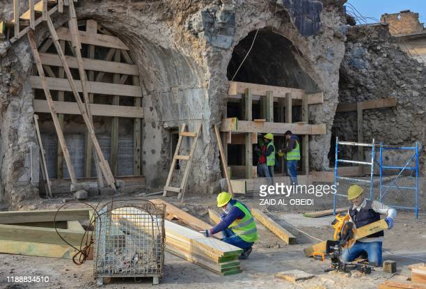 Iraqi workers build wooden supporting structures during the reconstruction of AlHadba leaning minaret in Mosuls warravaged old town on December 15...