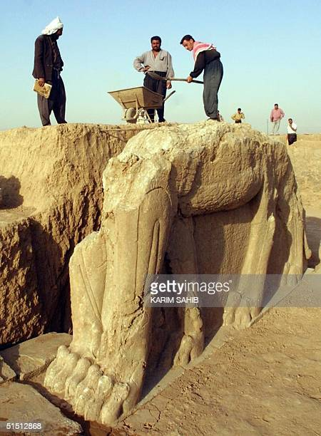 Iraqi workers clean a statue of winged bull at an archeological site in Nimrod 35 Kilometers southeast of the northern city of Mosul 17 July 2001...