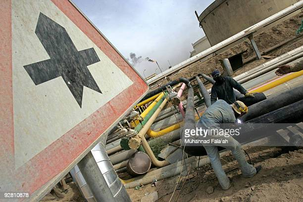 Iraqi workers cut pipes at the Daura oil refinery on November 5 2009 in Baghdad Iraq Iraq and a grouping of US and European oil companies Exxon Mobil...