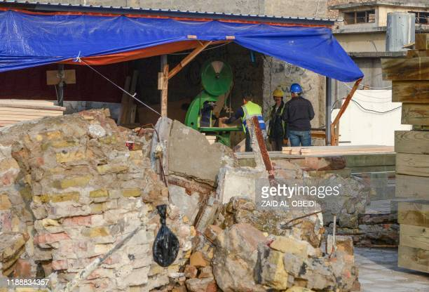 Iraqi workers cut wood for usage during the reconstruction of the AlHadba leaning minaret in Mosuls warravaged old town on December 15 2019 In...
