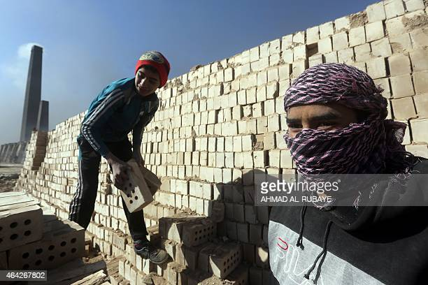 Iraqi workers pile bricks up at the traditional brick factory of Nahrawan one of the largest brick factories in Iraq located on the eastern outskirts...