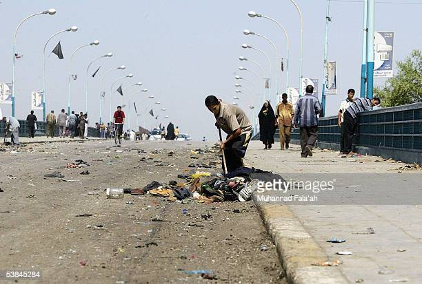Iraqi workers remove the belongings of Shiite pilgrims killed in a stampede on the al Aema Bridge September 1 2005 in Baghdad Iraq Funerals are being...
