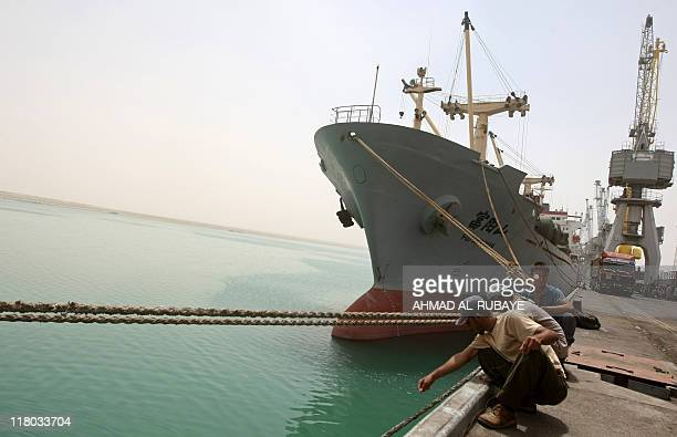 Iraqi workers squat near a ship emptying its load after docking at the Umm Qasr port in the southern Iraqi city of Basra on June 9 2011 AFP...
