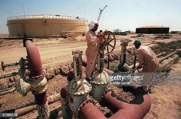Iraqi workers tend to pipes at an oil refinery in the southern Iraqi port of Basra 08 June 1999. Iraqi accusations that Kuwait has been stealing its...