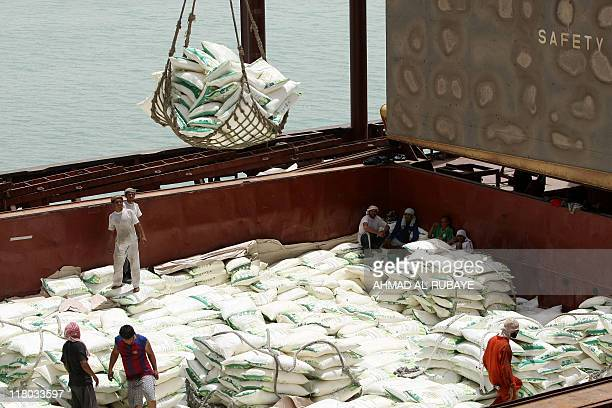 Iraqi workers unload goods from a cargo container at Umm Qasr port in the southern city of Basra on June 9 2011 AFP PHOTO/AHMAD ALRUBAYE