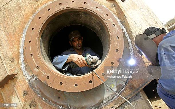 Iraqi workers weld an oil tank at the Daura oil refinery on November 5 2009 in Baghdad Iraq Iraq and a grouping of US and European oil companies...