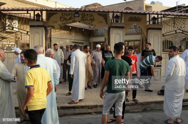Iraqi worshippers arrive to perform Eid alFitr prayers as they mark the religious holiday after the end of the holy month of Ramadan at a mosque...