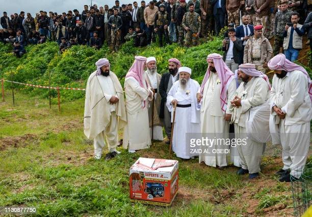 Iraqi Yazidi clerics attend the exhumation of a mass-grave of hundreds of Yazidis killed by Islamic State group militants in the northern Iraqi...