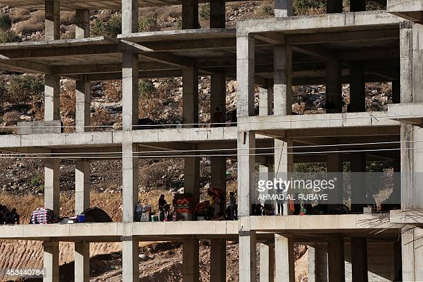 Iraqi Yazidis who fled their homes a week ago when Islamic State militants attacked the town of Sinjar gather inside a building under construction...