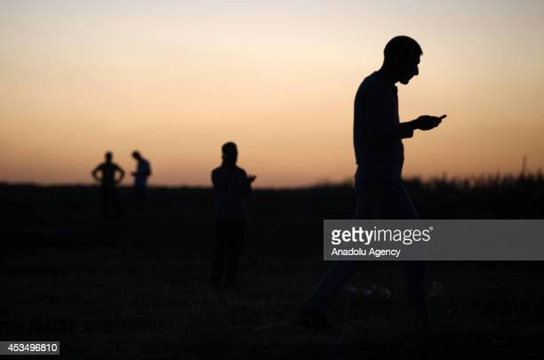 Iraqi Yezidi people try to get an efficient cell signal near cell towers in Sirnak, Turkey on August 11, 2014 in order to make phone calls to talk...