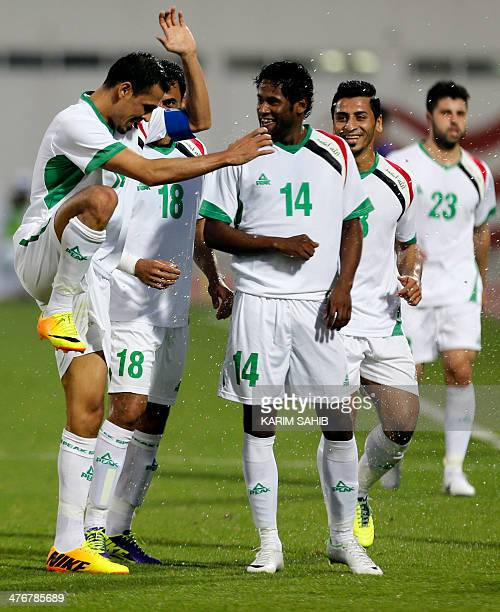 Iraqi Younes Mahmood celebrates with teammates after winning their qualification football match for the Asian Cup Australia 2015 China versus Iraq in...