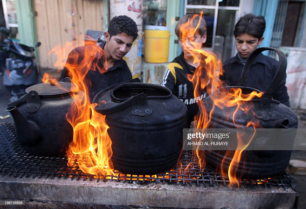 Iraqi youth look on, as pots of tea which will be served to Muslim Shiite pilgrims brew, as believers begin to gather for the upcoming Ashura rituals in Baghdad, on November 20, 2012. Ashura mourns the death of Imam Hussein, a grandson of the Prophet Mohammed, who was killed by armies of the caliph Yazid near Karbala in 680 AD.