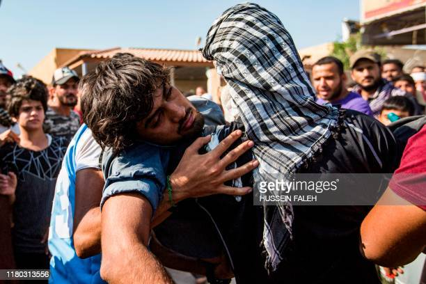 TOPSHOT Iraqi youths carry away an injured protester during a demonstration outside the southern port of Umm Qasr on November 5 after security forces...