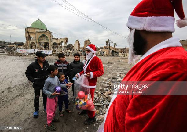 TOPSHOT Iraqi youths dressed in Father Christmas suits distribute gifts to children near the ruins of the Great Mosque of AlNuri in the old city of...