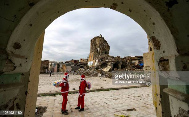 Iraqi youths dressed in Father Christmas suits look at the remains of 'AlHadba' leaning minaret in the ruins of the Great Mosque of AlNuri as they...