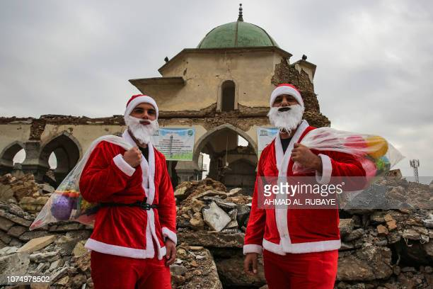 TOPSHOT Iraqi youths dressed in Father Christmas suits pose for a picture as they stand in the ruins of the Great Mosque of AlNuri as they distribute...