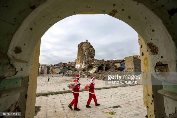 Iraqi youths dressed in Father Christmas suits walk past the remains of 'AlHadba' leaning minaret in the ruins of the Great Mosque of AlNuri as they...