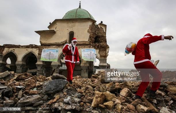 Iraqi youths dressed in Father Christmas suits walk through the ruins of the Great Mosque of AlNuri as they distribute gifts in the old city of Mosul...