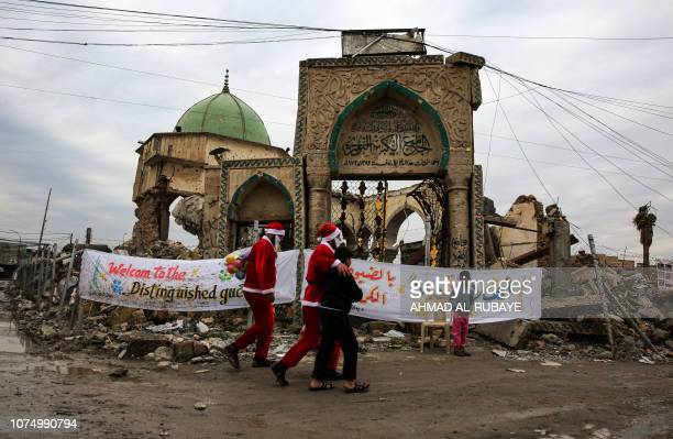 Iraqi youths dressed in Father Christmas suits walk with children by the ruins of the Great Mosque of AlNuri as they distribute gifts in the old city...
