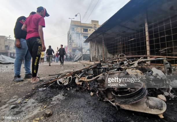 Iraqi youths look at a destroyed vehicle after clashes between anti-government protesters and supporters of firebrand Shiite cleric Moqtada Sadr, in...