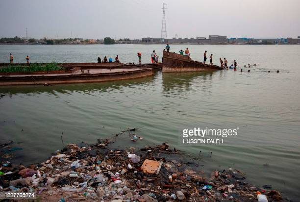 Iraqi youths play atop a sunken boat as rubbish, mainly plastic waste, floats in the Shatt Al-Arab river in the southern port city of Basra, on July...