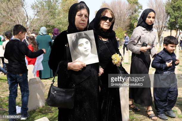 Iraqi-Kurds visit a grave site in Halabja near the monument for victims of the Halabja gas massacre that killed some 5,000 people as they mark the...