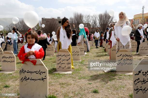 TOPSHOT IraqiKurds visit a grave site in Halabja near the monument for victims of the Halabja gas massacre that killed some 5000 people as they mark...