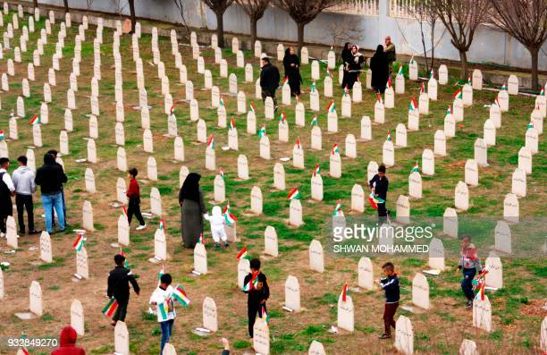 Iraqi-Kurds visit a grave site in Halabja on March 16 as they mark the 30th anniversary of the Halabja gas massacre that killed some 5,000 people....