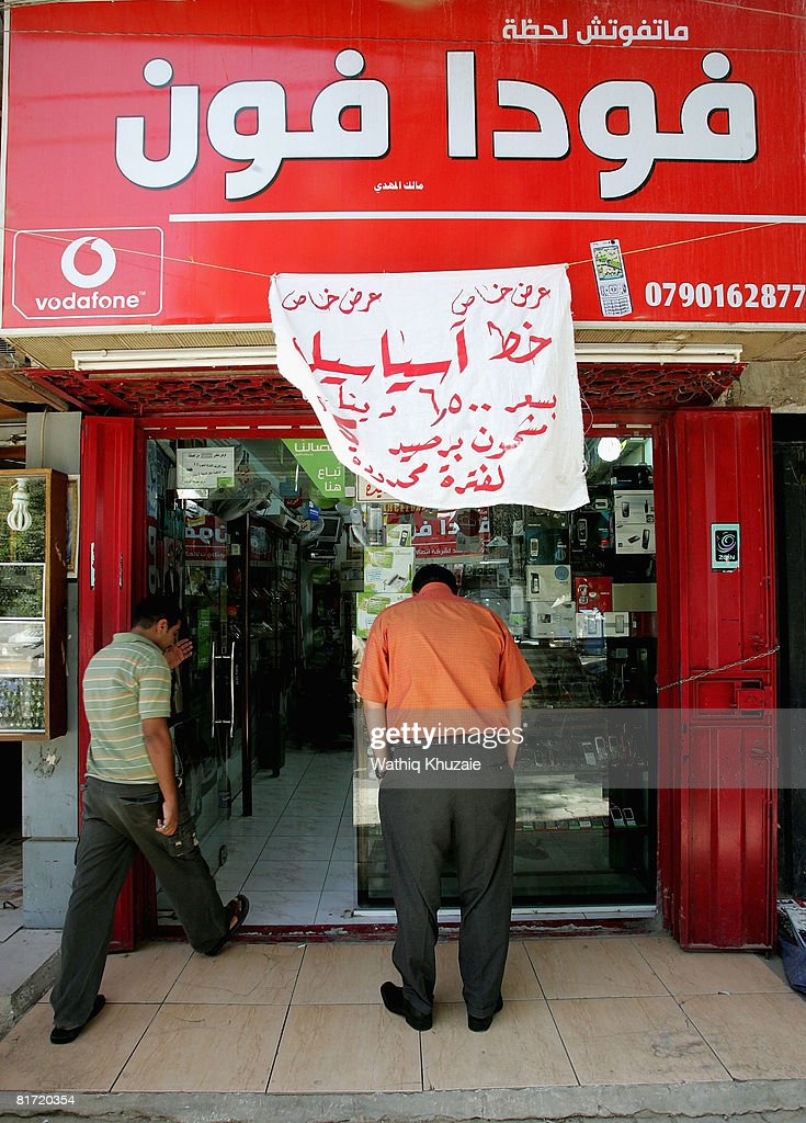 Iraqis are seen in front of a mobile phone store on June 26, 2008 in Baghdad, Iraq. The war-damaged aging landline telephone infrastructure means Iraqis are increasingly more dependent on mobile phones in daily life and business.