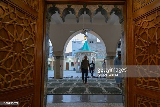 Iraqis arrive to perform the Eid AlAdha morning prayer at alBasha mosque in the eastern side of Iraq's northern city of Mosul on August 11 2019...