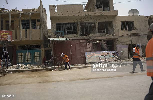 Iraqis begin to clean up streets in front of destroyed buildings after two months of fighting along Al Quds Street in Sadr City the 25 million Shia...