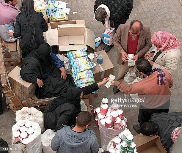 Iraqis buy smuggled goods from a street vendor in Baghdad 28 January. Most of the products available are smuggled from neighboring countries, as Iraq...