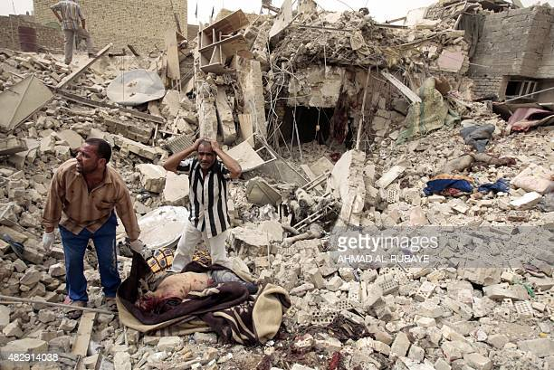 Iraqis call for help as they wait to carry away their dead neighbours from the ruins of a house hit in an alleged US air strike in Baghdad Sadr City...