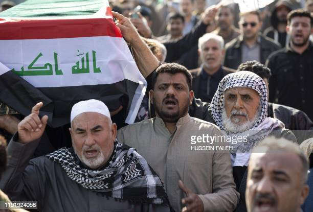 Iraqis carry a mock coffin as they march in a symbolic funeral procession for senior Iraqi military figure Abu Mahdi alMuhandis in the southern city...
