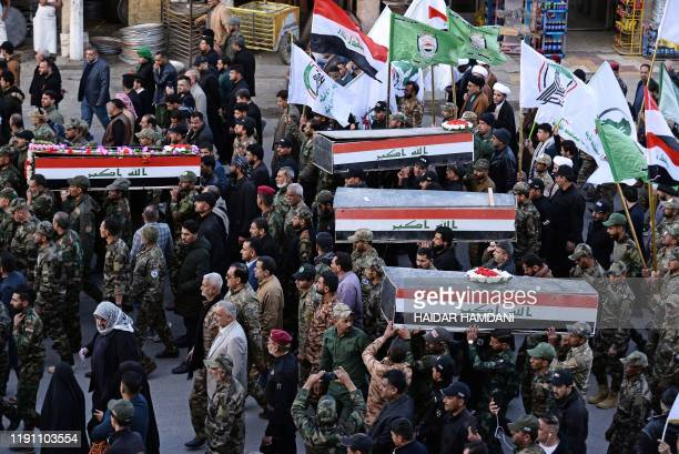 Iraqis carry coffins during a funeral procession in the central shrine city of Najaf on December 31 for Hashed alShaabi fighters who were killed on...