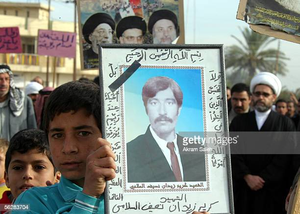 Iraqis carry pictures of some of the approximate 148 men who were allegedly killed by Saddam Hussein's regime as they take part in a demonstration...