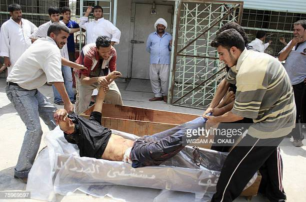 Iraqis carry the body of their killed relative into a plastic bag before putting him in a coffin after they took him out of the morgue of a hospital...