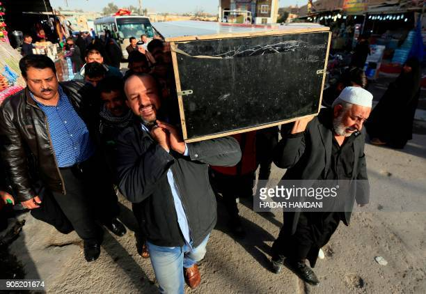 Iraqis carry the coffin of a victim during a funeral in the holy city of Najaf on January 15 following today's twin suicide bombing in the capital...