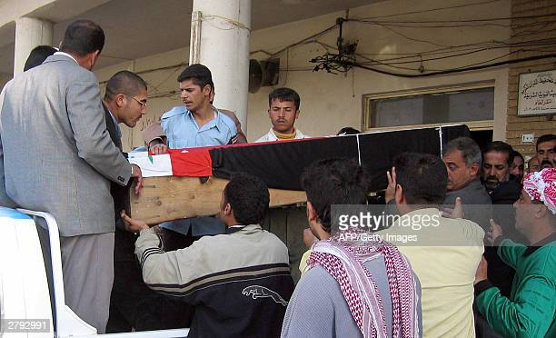 Iraqis carry the coffin of bomb disposal chief Captain Fallah Khadduri 08 December 2003 in Baquba 60 kms northeast of Baghdad The Iraqi police...