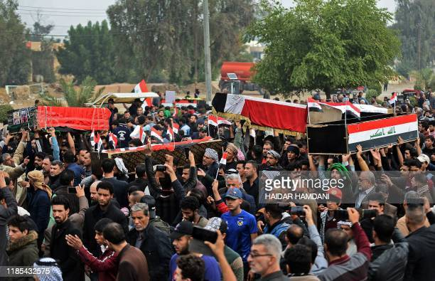 Iraqis carry the coffins of anti-government demonstrators killed during protests a day earlier, during a funeral procession in the central holy...