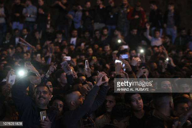Iraqis celebrate as fireworks burst above the Baghdad Tower in the Iraqi capital Baghdad on January 1 2019 during New Year celebrations as the tower...