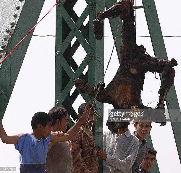 Iraqis chant antiAmericans slogans near a charred body hanging from a bridge over the Euphrates River in the flashpoint town of Fallujah 50 kms west...