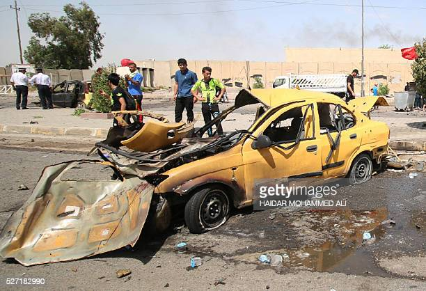 Iraqis check the damage following a car bomb targeting pilgrims heading to commemorate the death of Imam alKadhim in Baghdad's southern Saidiya...
