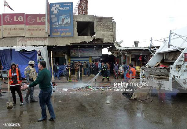 Iraqi's clean the street after a suicide bomber detonated explosives inside a restaurant in Baghdad alJadida east of the capital on February 7 2015...