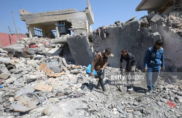Iraqis clean up the rubble of destroyed buildings in the Mosul alJadida area on March 26 following air strikes in which civilians have been...