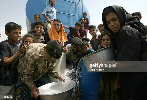 Iraqis collect drinking water from a tanker truck May 8 2003 in Basra Iraq The World Health Organization warned today of a possible cholera epidemic...
