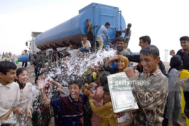 Iraqis collect drinking water from a tanker truck May 8, 2003 in Basra, Iraq. The World Health Organization warned today of a possible cholera...