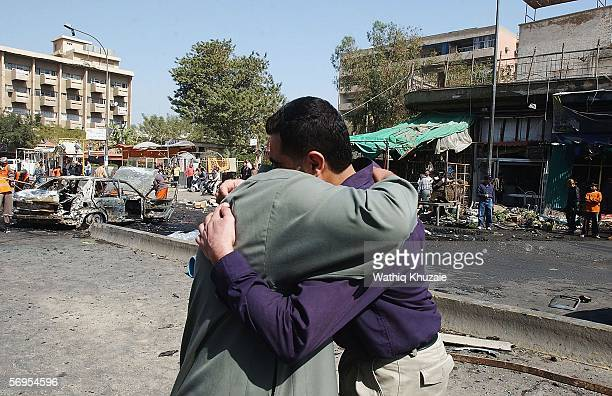 Iraqis comfort each others at the site of a car bomb explosion on February 28 2006 at a market in Karrada district of Baghdad Iraq Three simultaneous...